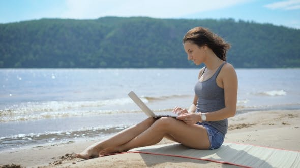 Thumbnail for Beautiful Sexy Young Inspirated Lady Is Sitting At a Beach Using Laptop