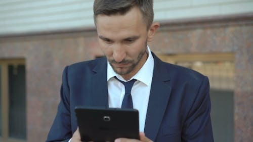 Angry Businessman Wants To Spoil Tablet But Stops.