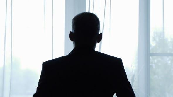 Man Wears a Jacket In Front Of a Window Contrast