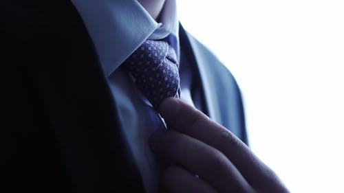 Man Ties a Necktie Knot And Straightens