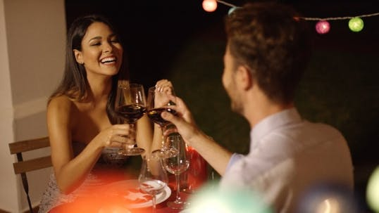 Cover Image for Couple Laughs As They Raise Their Wine Glasses