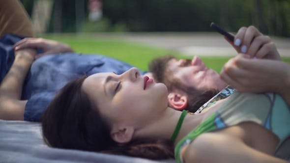 Thumbnail for Male And Female Relax Outdoors With Modern Device.