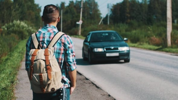 Thumbnail for Young Man With Backpack Hitchhiking At Road In Countryside. Summer Sunny Day