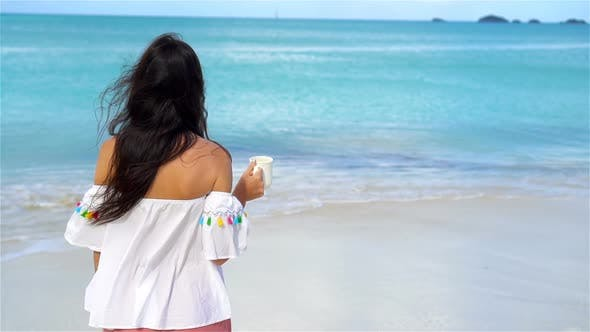 Thumbnail for Young Woman with Hot Coffee Enjoying Beach View. Beautiful Girl in Slow Motion Video