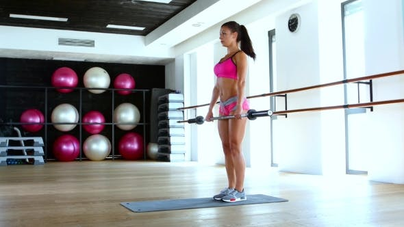 Cover Image for Woman With Barbell Flexing Muscles In Gym