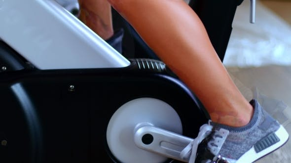 Thumbnail for Girl Engaged On a Stationary Bike In The Gym. Female Legs