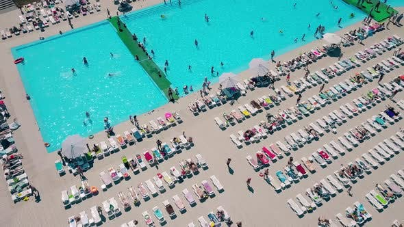 Aerial: Flying Over the Beach, Lot of People Are Sunbathing, Swimming in the Pool