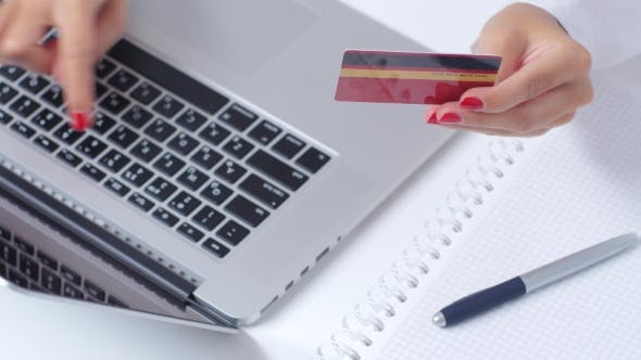 Thumbnail for Woman With Card In Hand Completes Online Shopping Through Laptop.