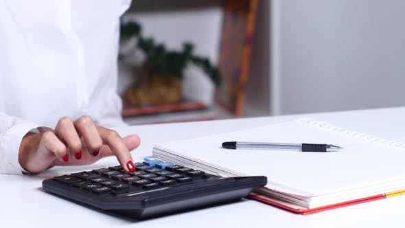 Thumbnail for Woman With Blueprint Counting On Calculator And Writing To Notebook.