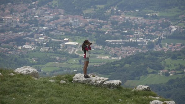 Thumbnail for Female Traveler Photographing Town From Mountain