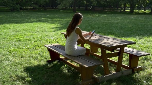 Thumbnail for Woman Texting And Browsing On Bench In Park