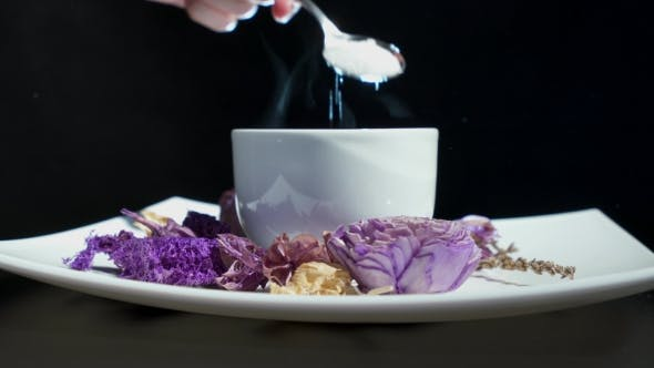 Thumbnail for Adding Sugar To Cup Of Tea With Flowers Rotating