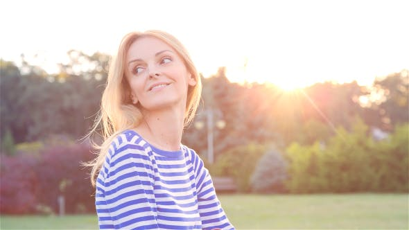 Thumbnail for Happy Beautiful Young Woman Sitting on the Grass in City Park and Smiling at Sunset 3