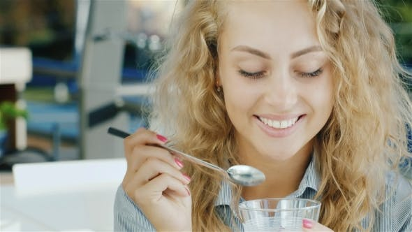 Thumbnail for Attractive Young Woman Eating Ice Cream in Cafe, Smiling at the Camera