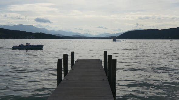 Thumbnail for Boat Passing by Wooden Dock in a Big Lake