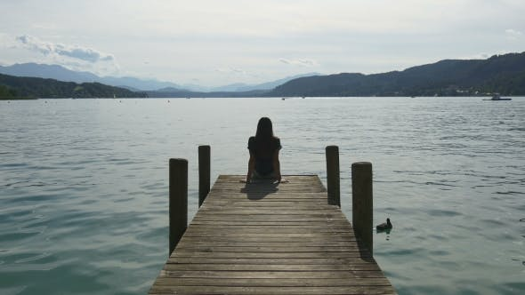Relaxation at Mountain Lake. Woman Sits on Dock