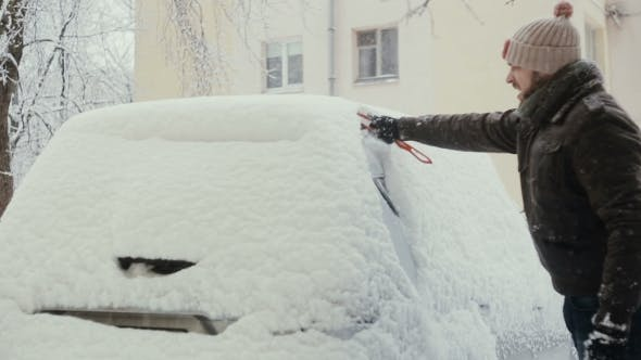 Thumbnail for Man Clears Snow From His Car On The Street In Winter, Back View,