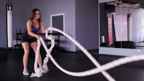 Thumbnail for Junge Frau Durchführung Übung mit Seilen im Fitnessstudio
