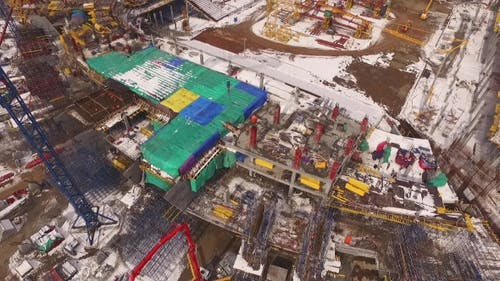 Aerial Top View Of Stadium Construction, Moving Construction Materials By Huge Crane, Winter Time