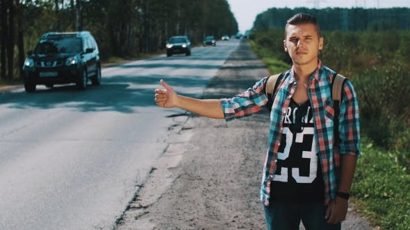Thumbnail for Young Man With Backpack Hitchhiking At Road In Countryside. Thumbing Up. Travel
