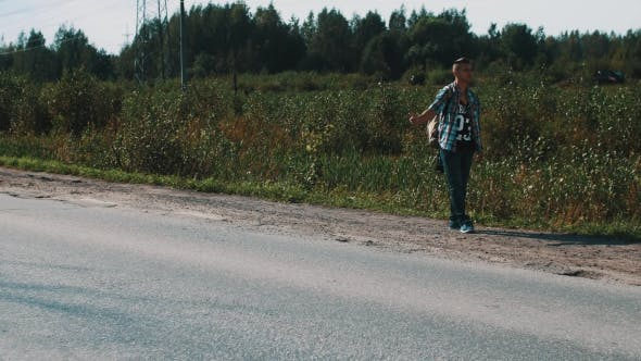 Thumbnail for Man Stay At Road In Countryside. Hitchhiking. Thumb Up. Smoke Cigarette. Travel