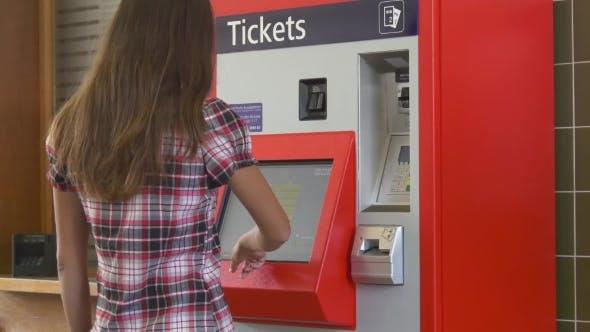 Woman Buying Ticket In Ticketing Machine
