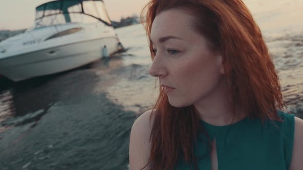 Thumbnail for Attractive Red Hair Girl In Turquoise Dress On Motor Boat
