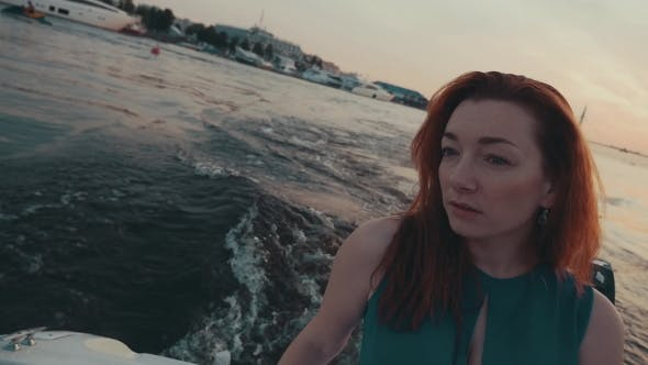 Thumbnail for Pretty Red Hair Girl In Turquoise Dress On Motor Boat. Summer Evening. Scenery