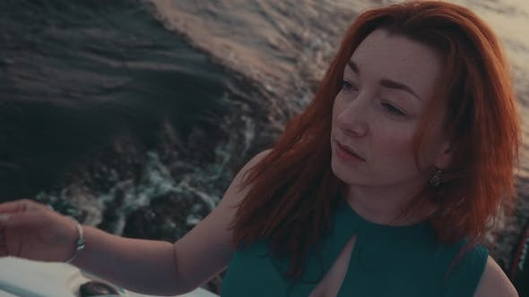 Thumbnail for Pretty Red Hair Girl In Turquoise Dress On Motor Boat. Evening. Touch Hair.