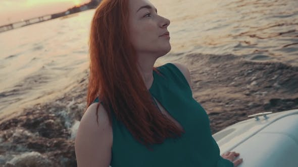 Thumbnail for Pretty Red Hair Girl In Turquoise Dress Relax On Motor Boat. Summer Evening.