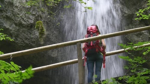 Ecotourism. Hiking Woman Watch Watches a Waterfall