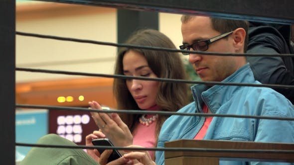 Thumbnail for Brunette Girl And Man In Glasses Using Their Mobile Phones In a Cafe