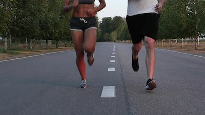 Sportsman and Sportswoman Running on the Center of the Road