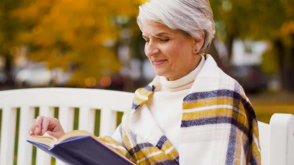 Thumbnail for Happy Senior Woman Reading Book at Autumn Park 32