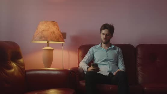 Guy looks at the smartphone sitting on the red sofa at home