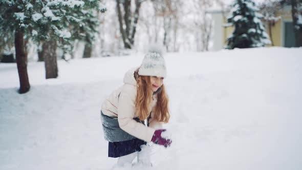 Thumbnail for Fille souriante aux cheveux longs lance des boules de neige dans la rue