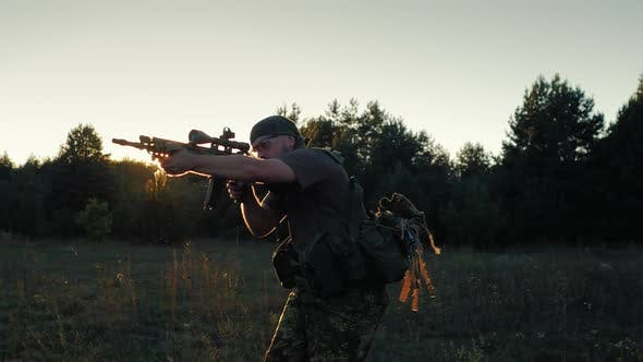 Thumbnail for Steadicam Shot: Soldier in Camouflage Attack. In the Rays of a Sunset in Arms