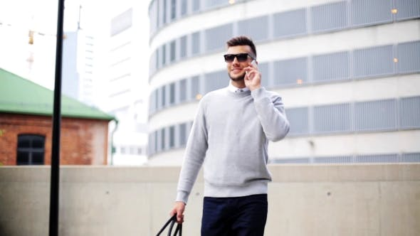 Cover Image for Young Man With Smartphone And Bag Walking In City