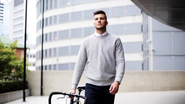 Cover Image for Young Man Walking Along City Street With Bicycle