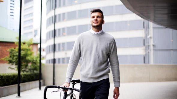 Thumbnail for Young Man Walking Along City Street With Bicycle