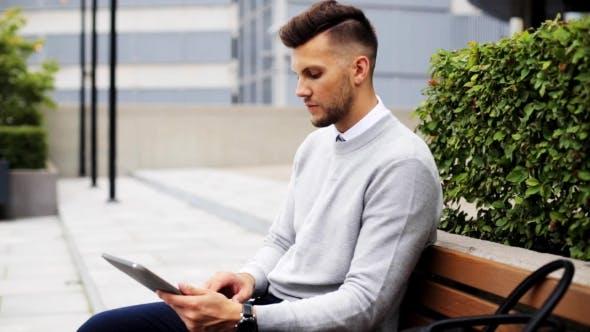 Thumbnail for Mann mit Tablet PC sitzend auf Stadt Straße Bank