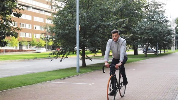Thumbnail for Young Man Riding Bicycle On City Street