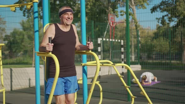 Thumbnail for A Retired Elderly Man Works Out on a Sports Ground Outside. Healthy Lifestyle Concept.