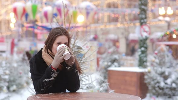 Thumbnail for Beautiful Young Woman Drinking Hot Tea During Christmas Fair