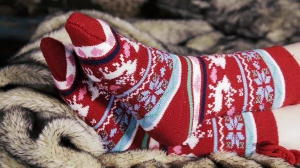 Thumbnail for Female Legs In Christmas Socks Under a Blanket