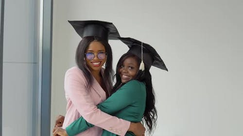 Two Girlfriends Graduates in Festive Costumes and Master's Hats Hug and Look at the Camera with a