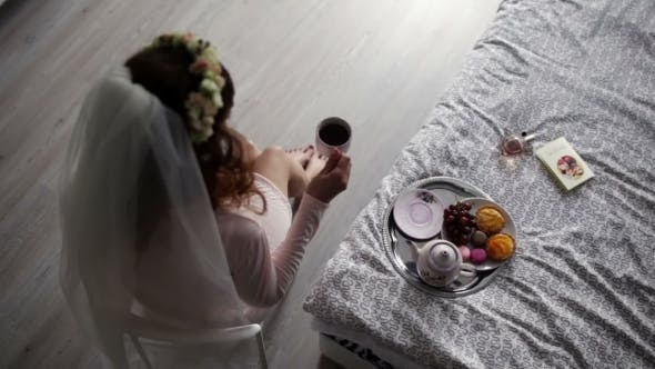 Thumbnail for Bride Is Sitting On a Chair And Drinking Coffee.