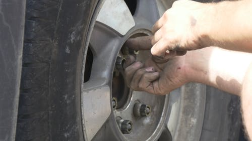 Man Replaces Tire On a Roadside