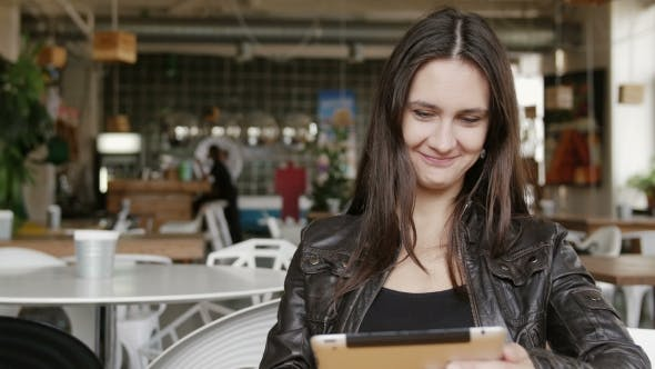 Thumbnail for Stylish Young Woman Uses a Tablet and Sends Sms