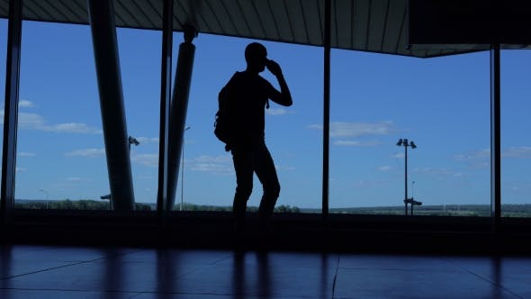 Thumbnail for Young Man With a Backpack Standing In An Airport Lounge And Talking On The Phone.